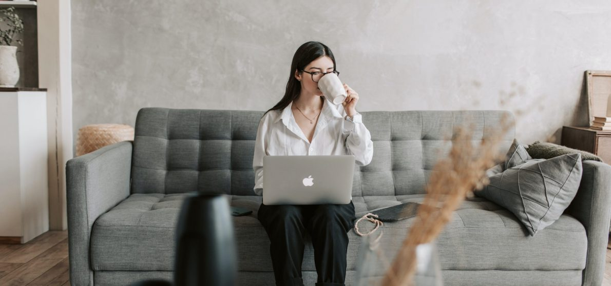 woman-drinking-coffee-while-working-with-laptop-4050289